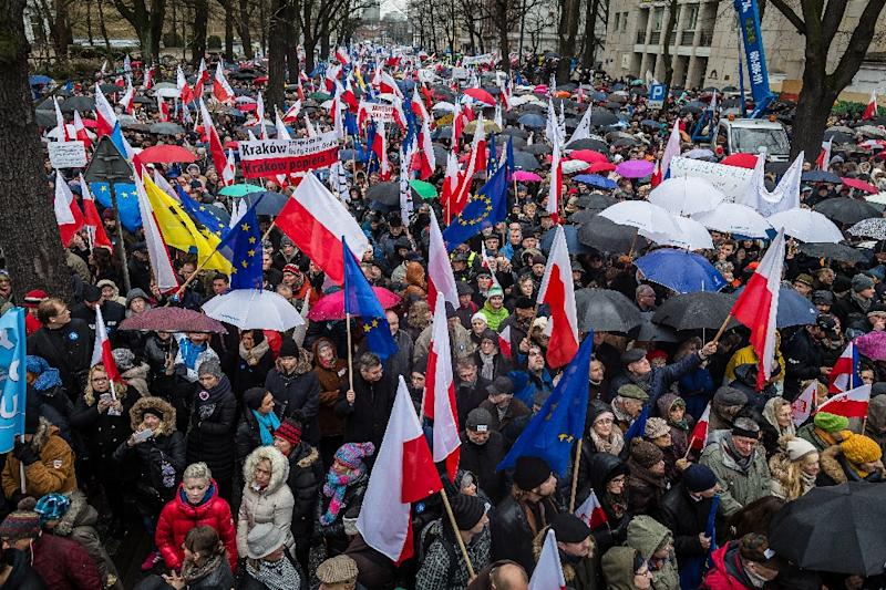 People hold Polish national flags and European flags during an anti-government demonstration in central Warsaw on December 12, 2015