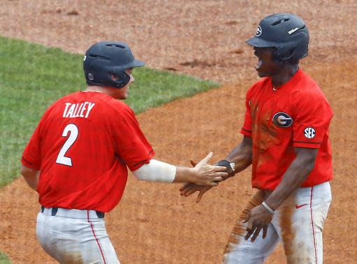 Georgia's LJ Talley (2) and Ivan Johnson (3) celebrate after both score to tie the game on a wild throw to home plate by Mississippi pitcher Parker Caracci (65) during the eighth inning of a Southeastern Conference Tournament NCAA college baseball game, Thursday, May 24, 2018, in Hoover, Ala. (AP Photo/Butch Dill)