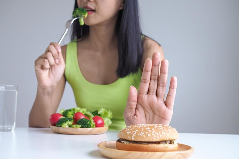 Healthy women choose to eat vegetable trays and refuse to eat hamburgers.