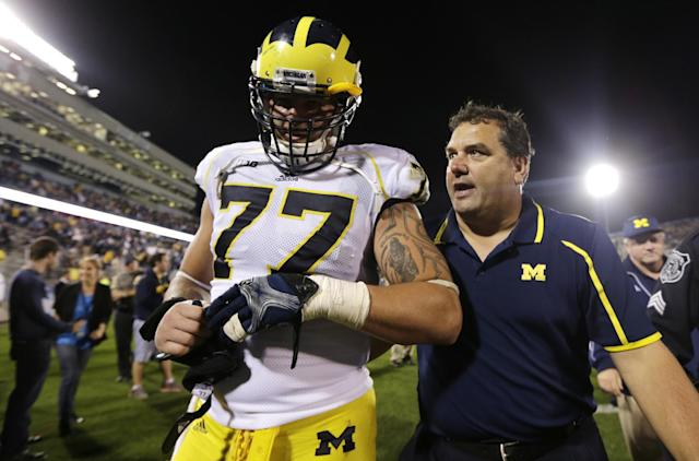 Michigan head coach Brady Hoke, right, talks with offensive linesman Taylor Lewan (77) after a win against Connecticut during an NCAA college football game, Saturday, Sept. 21, 2013, in East Hartford, Conn. Michigan won 24-21. (AP Photo/Charles Krupa)