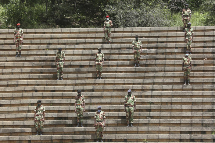"""Soldiers practice social distancing during a state burial of government ministers who died of COVID-19, in Harare, Thursday, Jan. 21, 2021. Zimbabwean President Emmerson Mnangagwa who presided over the burial called the pandemic """"evil"""" and urged people to wear masks, practice social distancing and sanitize, as cases across the country increased amid a fragile health system. (AP Photo/Tsvangirayi Mukwazhi)"""