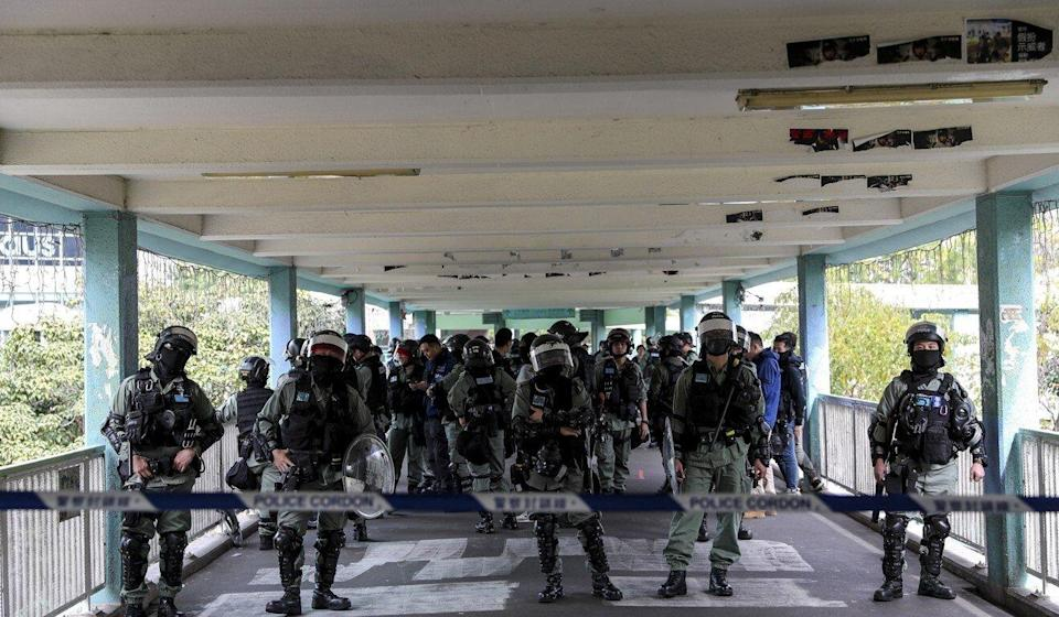 Riot police stand guard on the footbridge outside Landmark North shopping centre in Sheung Shui. Photo: Sam Tsang