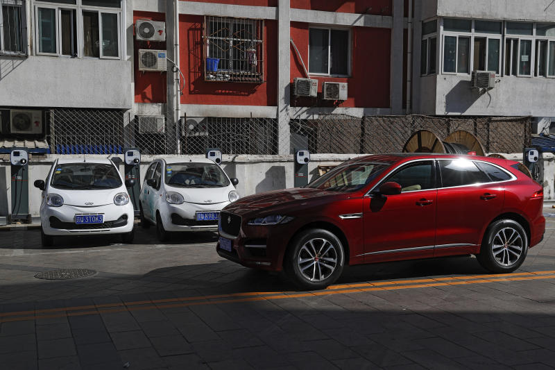 FILE - In this Friday, April 14, 2017, file photo, an SUV drives past electric cars parked at a charging station outside a residential building in Beijing. Momentum is building worldwide for electric cars thanks to rising government fuel economy standards and climate concerns. Automakers are jumping on board. But selling those cars will be difficult unless the world builds more charging stations. (AP Photo/Andy Wong, File)
