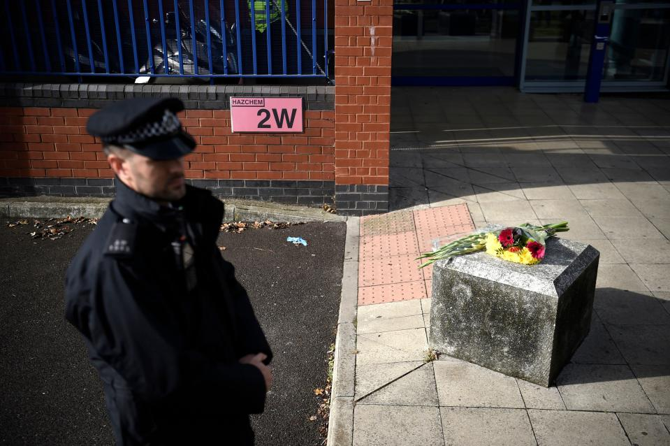 A police officer stands near flowers placed outside the Croydon Custody Centre in south London on September 25, 2020, following the shooting of a British police officer by a 23-year-old man being detained at the centre. - A British police officer was shot dead in the early hours of Friday morning, Scotland Yard said, the first officer to be killed by gunfire while on duty in over eight years. (Photo by DANIEL LEAL-OLIVAS / AFP) (Photo by DANIEL LEAL-OLIVAS/AFP via Getty Images)