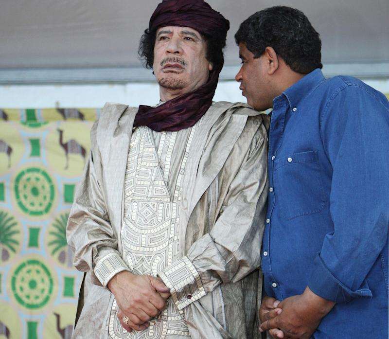 FILE - In this Tuesday, Oct. 6, 2009  file photo, intelligence chief Abdullah al-Senoussi, right, whispers to Libyan leader Moammar Gadhafi in Sabha, Libya. A government statement read on national radio states that Mauritania has agreed to extradite Moammar Gadhafi's former spy chief, months after he tried to slip into Mauritania wearing a disguise and traveling on a fake passport. An official said Al-Senoussi is already on a plane headed to Libya. (AP Photo/Abdel Magid al-Fergany, File)