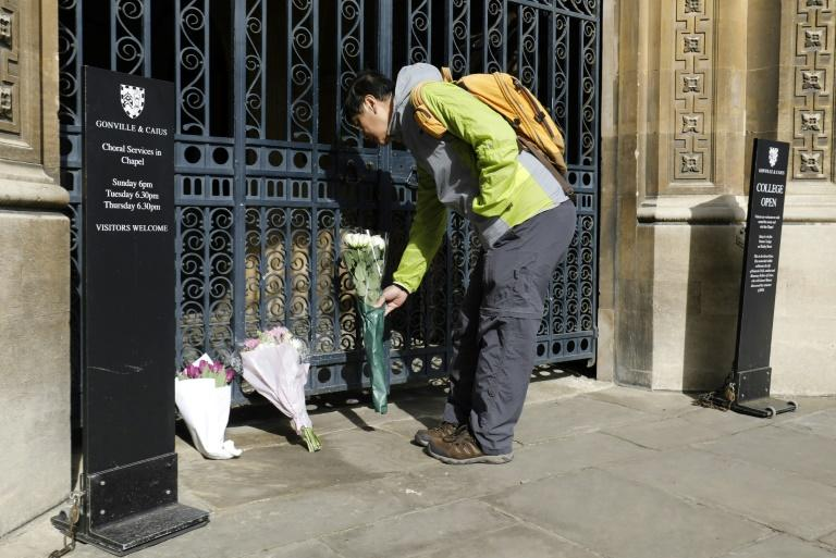 Well-wishers such as this man laying flowers outside Gonville and Caius College, Cambridge, where Stephen Hawking worked  to unlock the secrets of the universe, have flocked to pay tribute to the physicist, whose funeral will be March 31