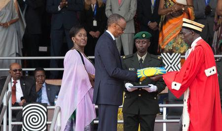Rwanda's newly inaugurated President Paul Kagame (C) receives the National flag from Chief Justice Sam Rugege next to First Lady Jeannette Kagame after taking the oath of office during his swearing-in ceremony at Amahoro stadium in Kigali, Rwanda, August 18, 2017. REUTERS/Jean Bizimana