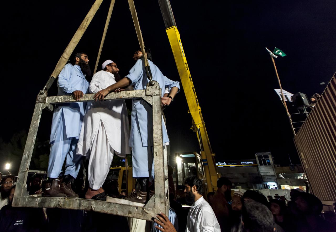 Hafiz Saeed (2nd L), head of the Jamaat-ud-Dawa organisation, is lifted up with a crane to the top of a container used as a podium, to address his supporters during a rally marking Pakistan's Defense Day in Islamabad September 6, 2013. REUTERS/Zohra Bensemra (PAKISTAN - Tags: ANNIVERSARY POLITICS)