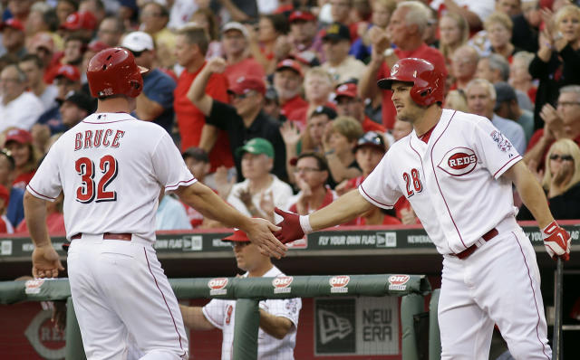 Jay Bruce (32) is congratulated by Chris Heisey, right, after scoring on a base hit by Devin Mesoraco off of Boston Red Sox pitcher Joe Kelly in the first inning of a baseball game, Tuesday, Aug. 12, 2014, in Cincinnati. (AP Photo/Tony Tribble)