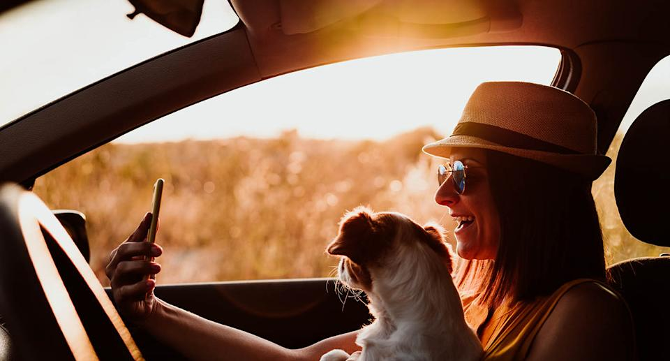 A woman takes a selfie with a dog in a car. Source: Getty Images