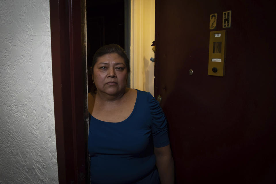 Candida Uraga poses for a photo in the doorway of her apartment in New York, Friday, March 19, 2021. She has struggled to pay rent after being laid off from her job as a teaching assistant during the pandemic, and was denied help under a federally-funded rental assistance program. (AP Photo/Robert Bumsted)