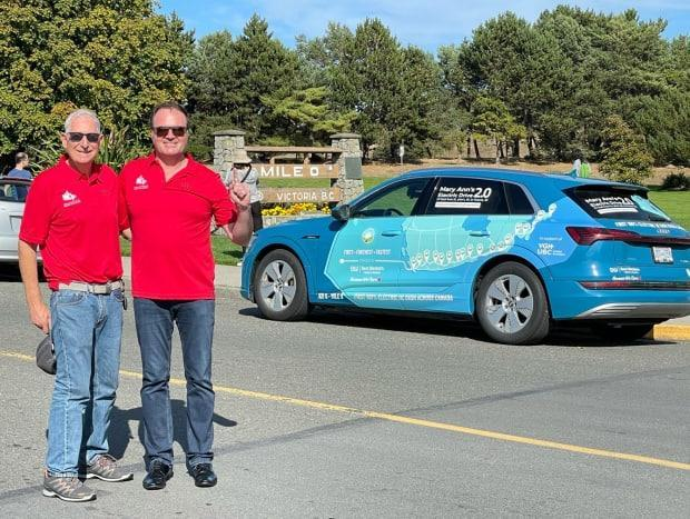 Harvey Stoicher (left) and Kent Rathwell pose with their electric Audi at Mile Zero in Victoria on Sept. 18. Their journey across Canada in August took them four days and 19 hours, including ferries and charging. (Kent Rathwell/Sun Country Highway - image credit)