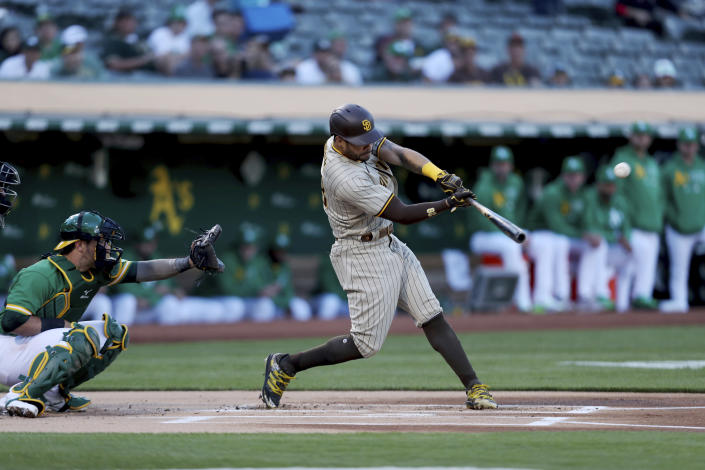 San Diego Padres' Tommy Pham, right, hits a home run in front of Oakland Athletics' Yan Gomes during the first inning of a baseball game in Oakland, Calif., Tuesday, Aug. 3, 2021. (AP Photo/Jed Jacobsohn)