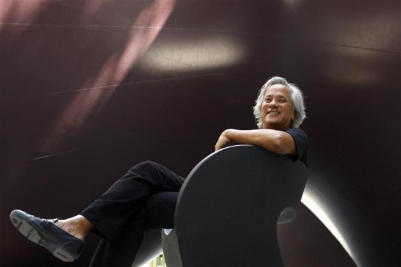 "Artist Anish Kapoor poses for the media next to his set-up ""Leviathan"" for the Monumenta 2011 event in the nave of the ""Grand Palais"" in Paris May 9, 2011."