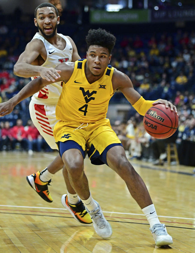 West Virginia guard Miles McBride (4) drives on Youngstown State guard Christian Bentley (5) during the first half of an NCAA college basketball game, Saturday, Dec. 21, 2019, in Youngstown, Ohio. (AP Photo/David Dermer)