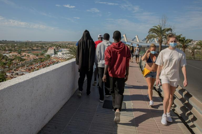 Malian migrants walk past a group of tourists in Gran Canaria, after being rescued by the Spanish coast guard
