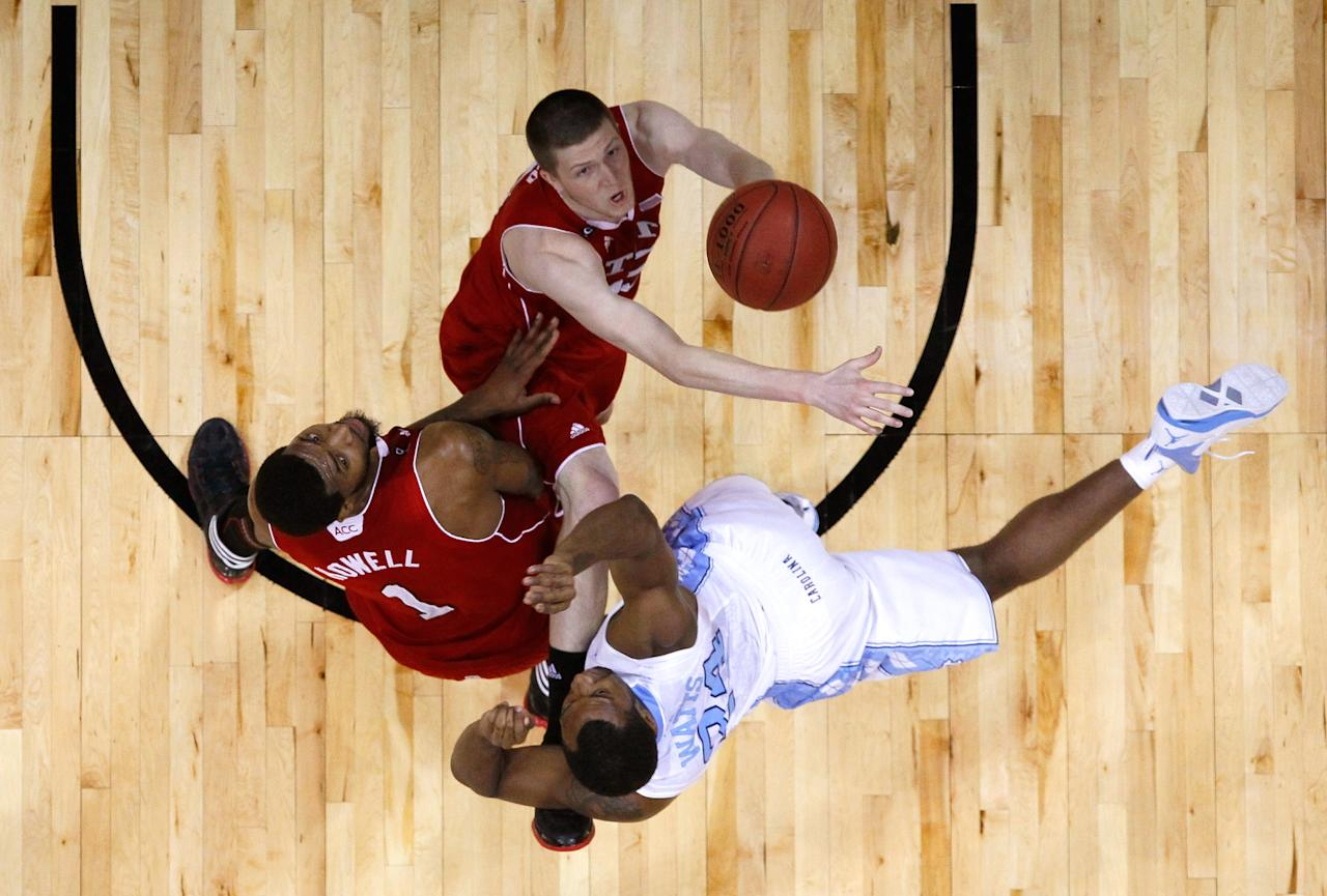 ATLANTA, GA - MARCH 10:  Justin Watts #24 of the North Carolina Tar Heels shoots against Richard Howell #1 and Scott Wood #15 of the North Carolina State Wolfpack during the semifinals of the 2012 ACC Men's Basketball Conference Tournament at Philips Arena on March 10, 2012 in Atlanta, Georgia.  (Photo by Kevin C. Cox/Getty Images)