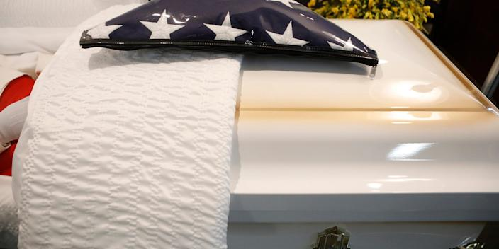 """TAMPA, FL - AUGUST 12: An American flag sits on top of a casket for a veteran who died of COVID-19 before his funeral at Ray Williams Funeral Home on August 12, 2020 in Tampa, Florida. <p class=""""copyright"""">Octavio Jones/Getty Images</p>"""
