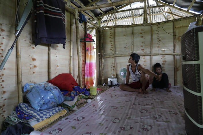Ronnel Manjares, left, and Trisha May Noche, right, stay inside their house as the rain pours in Tanauan, Batangas province, Philippines, Wednesday, July 15, 2020. Their 16-day-old son Kobe Manjares was heralded as the country's youngest COVID-19 survivor. But the relief and joy proved didn't last. Three days later, Kobe died on June 4 from complications of Hirschsprung disease, a rare birth defect. (AP Photo/Aaron Favila)