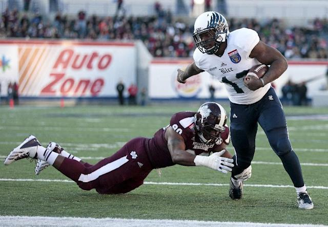Rice running back Charles Ross, right, evades Mississippi State defensive lineman Denico Autry as Ross scores a touchdown on a 1-yard run in the first quarter of the Liberty Bowl NCAA college football game on Tuesday, Dec. 31, 2013, in Memphis, Tenn. (AP Photo/Mark Humphrey)