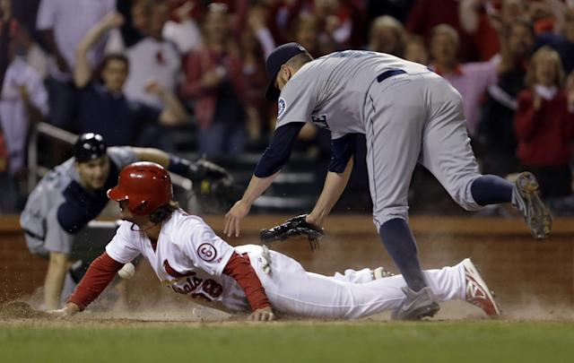 St. Louis Cardinals' Pete Kozma scores the game-winning run on a passed ball as Seattle Mariners relief pitcher Oliver Perez, right, covers home and catcher Mike Zunino, left, watches during the 10th inning of a baseball game Friday, Sept. 13, 2013, in St. Louis. The Cardinals won 2-1. (AP Photo/Jeff Roberson)