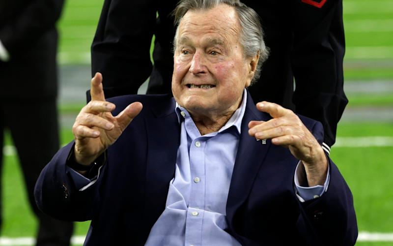 Former US president George HW Bush has been accused of groping women while they pose for pictures with him - AP