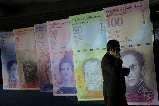 Posters depicting Venezuelan bolivares currency notes in Caracas on August 17, 2012