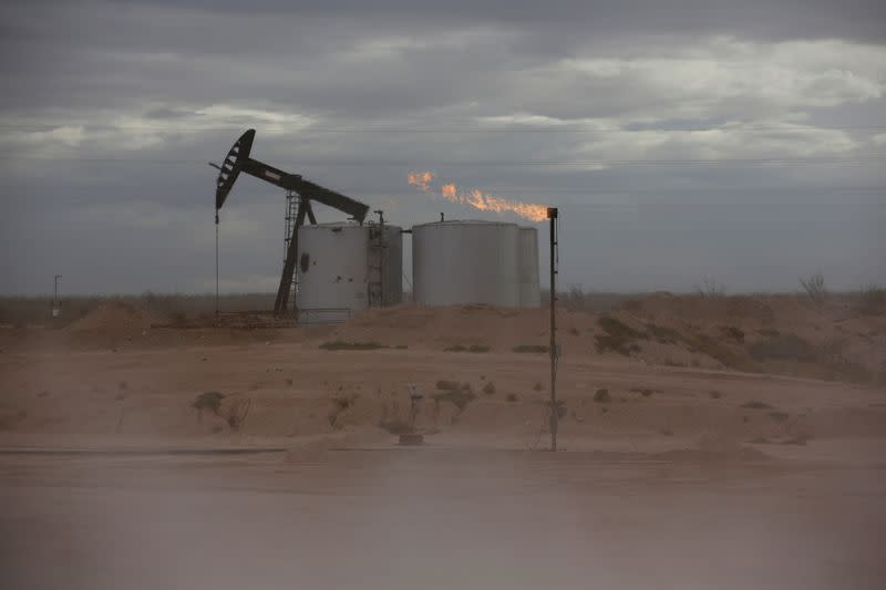 Dust blows around a crude oil pump jack and flare burning excess gas at a drill pad in the Permian Basin in Loving County