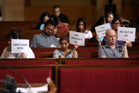 Immigrant supporters protest during the Los Angeles City Council ad hoc committee on immigration meeting to discuss the city's response to threats by the Trump administration to cut funding from Los Angeles