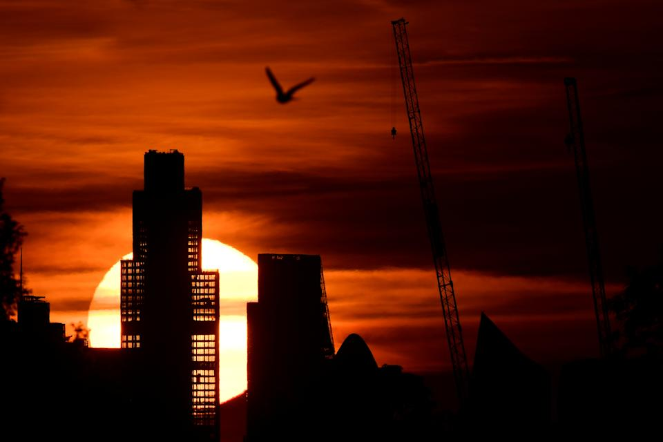 The Sun is seen rising behind skyscrapers of the City of London financial district, as the spread of the coronavirus disease (COVID-19) continues in Britain, June 2, 2020. REUTERS/Toby Melville