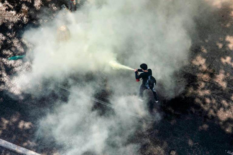 A protester uses a fire extinguisher as security forces crack down on demonstrations against the military coup in Yangon