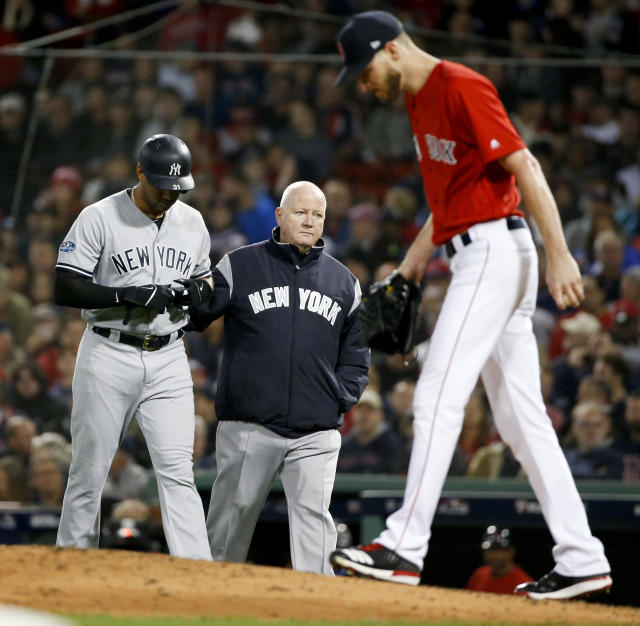 New York Yankees' Aaron Hicks, left, is helped off he field after getting hurt during the fourth inning of Game 1 of the baseball team's American League Division Series against the Boston Red Sox on Friday, Oct. 5, 2018, in Boston. (AP Photo/Elise Amendola)