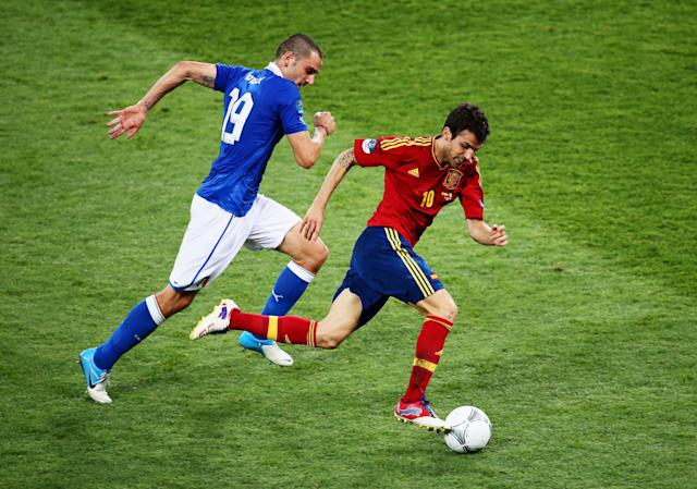 KIEV, UKRAINE - JULY 01: Cesc Fabregas (R) of Spain runs with the ball past Leonardo Bonucci of Italy during the UEFA EURO 2012 final match between Spain and Italy at the Olympic Stadium on July 1, 2012 in Kiev, Ukraine. (Photo by Martin Rose/Getty Images)