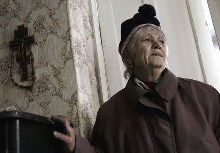 A woman reacts as she walks through a house damaged in what locals said was recent shelling, in the suburbs of Donetsk January 30, 2015. REUTERS/Alexander Ermochenko