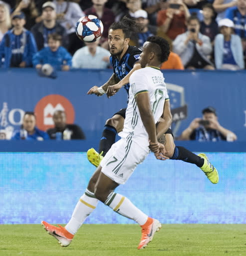 Montreal Impact's Maximiliano Urruti, rear, shoots as Portland Timbers' Jeremy Ebobisse defends during the second half of an MLS soccer match in Montreal, Wednesday, June 26, 2019. (Graham Hughes/The Canadian Press via AP)