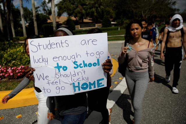 <p>Students from West Boca Raton Community High School carry a placard as they walk to Marjory Stoneman Douglas High School, during a protest to show support, following a mass shooting in Parkland, Fla., Feb. 20, 2018. (Photo: Carlos Garcia Rawlins/Reuters) </p>
