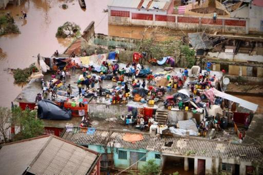 People gather on the roof of a house in Buzi. Some survivors say they have lost all their possessions