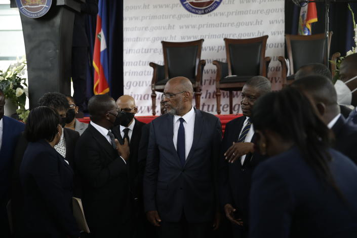 New Prime Minister Ariel Henry, center, talks with former interim Prime Minister Claude Joseph as they stand surrounded by Henry's cabinet after his appointment in Port-au-Prince, Haiti, Tuesday, July 20, 2021, weeks after the assassination of President Jovenel Moise at his home. (AP Photo/Joseph Odelyn)