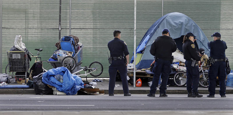 San Francisco police officers wait while homeless people collect their belongings in San Francisco in 2016.