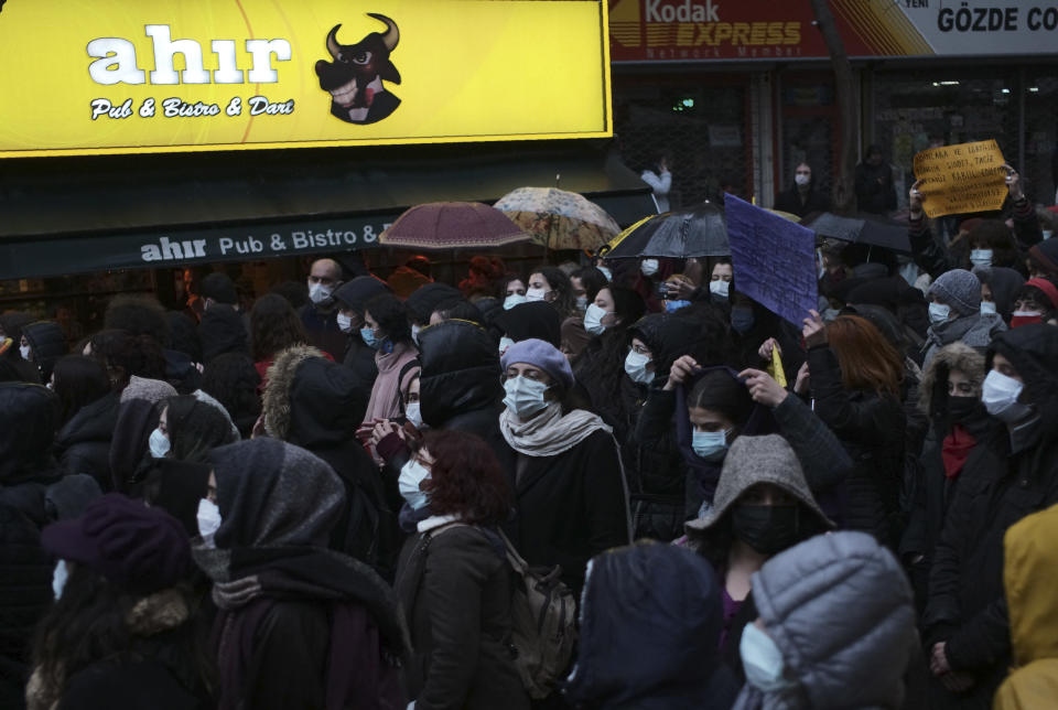 """Women wearing masks to protect against the spread of coronavirus, walk in the rain during a women's right protest, in Ankara, Turkey, Saturday, March 20, 2021. Turkey's weekly geographic COVID-19 figures keep increasing according to Health ministry statistics released late Saturday as the country continues its """"controlled normalization."""" (AP Photo/Burhan Ozbilici)"""