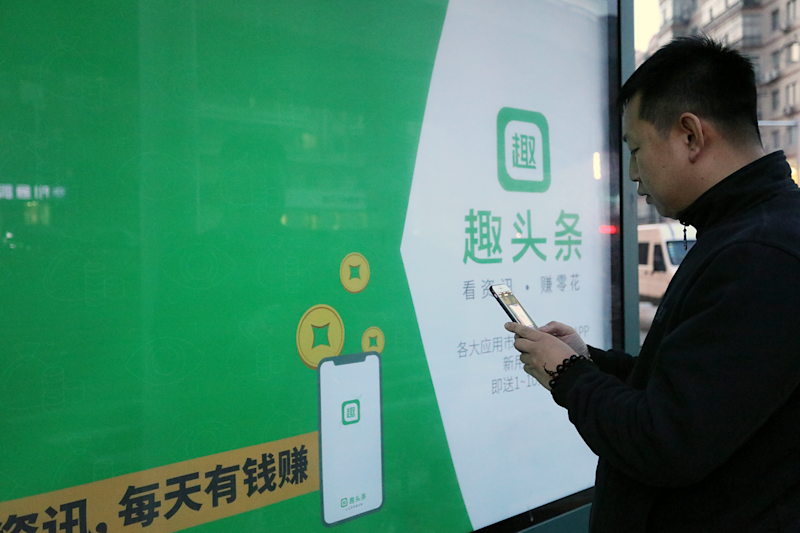 Mobile user in front a Qutoutiao sign.