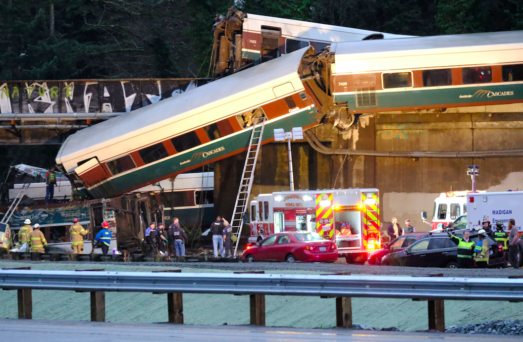 <p>The train derailed from the track and carriages fell onto the road below. (Rex) </p>