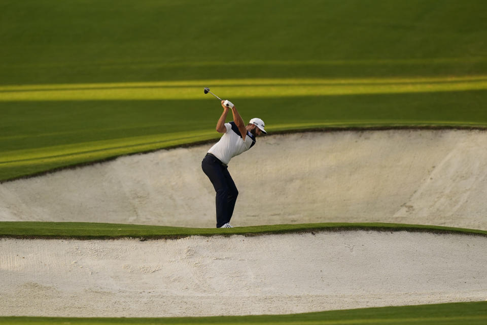 Dustin Johnson hits out of a bunker on the eighth hole during the first round of the Masters golf tournament Thursday, Nov. 12, 2020, in Augusta, Ga. (AP Photo/David J. Phillip)