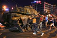 FILE PHOTO: People react near a military vehicle during an attempted coup in Ankara