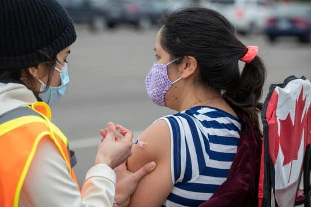 A person receives a COVID-19 vaccine at a drive-thru clinic at Richardson Stadium in Kingston, Ont. (Lars Hagberg/The Canadian Press - image credit)