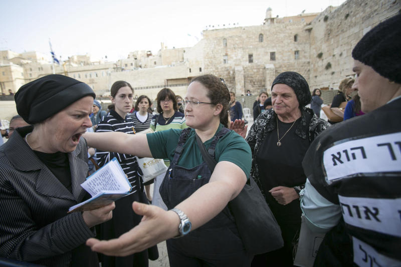 "An Israeli member of the ""Woman of the Wall"" organization, right, tries to hug an ultra-Orthodox woman as they pray at the Western Wall, the holiest site where Jews can pray, in Jerusalem's old city, Sunday, June 9, 2013. The group, known as ""Women of the Wall,"" convenes monthly prayer services at the Western Wall, wearing prayer shawls and performing rituals that ultra-Orthodox Jews believe only men are allowed to do. (AP Photo/Michal Fattal) ISRAEL OUT"