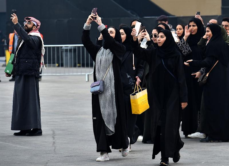 Saudi women take photographs with their mobile phones pior to the 2018 Saudia Ad Diriyah E-Prix Formula E Championship in Riyadh, on December 15, 2018 (AFP Photo/FAYEZ NURELDINE)