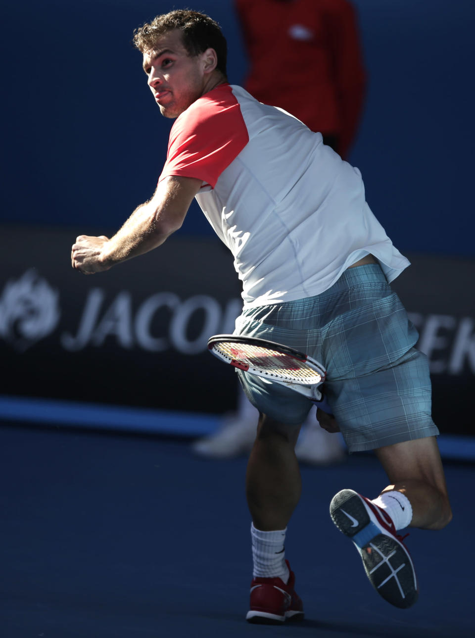 Grigor Dimitrov of Bulgaria hits a return between legs to Rafael Nadal of Spain during their quarterfinal at the Australian Open tennis championship in Melbourne, Australia, Wednesday, Jan. 22, 2014.(AP Photo/Rick Rycroft)