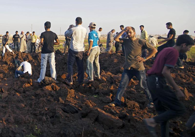 Syrian men inspect a hole allegedly made during an airstrike by government forces in the town of Marea, some 35 km ( 21 miles ) north of Aleppo , Syria, Monday, Aug. 13, 2012. (AP Photo/ Khalil Hamra)