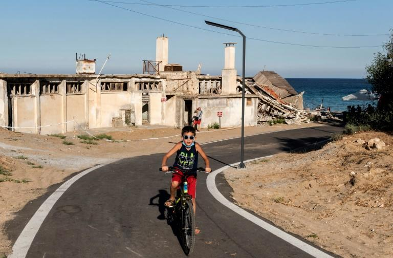A child rides a bicycle on a street lined with derelict buildings in the fenced-off area of Varosha in northern Cyprus in June 2019 ahead of Turkish-backed plans to reopen the resort (AFP/Iakovos Hatzistavrou)